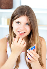 Pretty woman using cosmetic cream for her lips