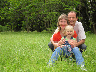 Happy family with little girl sits on meadow