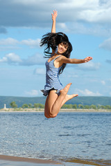 The happy young jumping woman