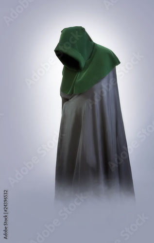 Man in an medieval hood and cloak in the fog