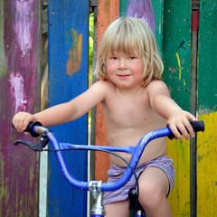 Kind am Fahrrad vor bunten Brettern