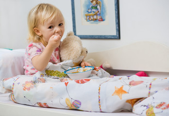little girl eating in bed