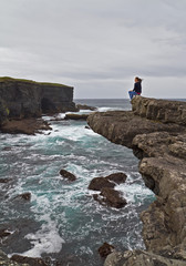 Woman sitting on the edge of the cliff in Kilkee