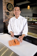 Japanese chef slicing raw fish for sushi
