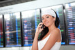 Young pretty woman talking on mobile phone in the airport