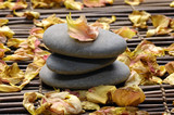 Stack of stone with rose withered petals on bamboo mat poster