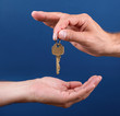 Hands handing over house key