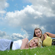 Two girl friends laying in grass