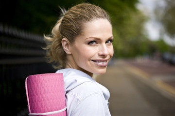 Portrait of a mid adult woman carrying a yoga mat