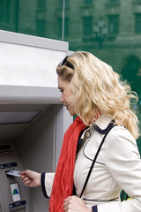 A mid adult woman using a cash machine