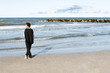 Young businessman in contemplation looking at ocean