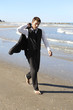 Young businessman in suit walking barefoot on beach