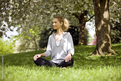 A mid adult woman sitting crosslegged under a tree