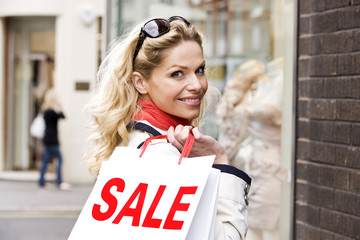 Portrait of a mid adult woman carrying sale bags