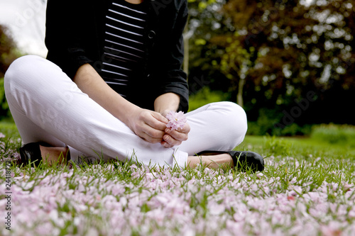 A woman sitting on the grass, holding spring blossom