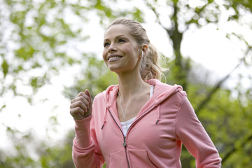 A mid adult woman jogging in the park, wearing headphones