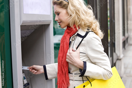 A mid adult woman using a cash machine, carrying a shopping bag