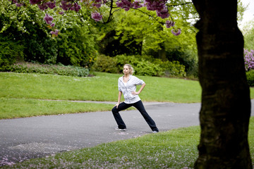A female runner stretching in the park