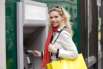 A mid adult woman using a cash machine, looking at camera