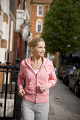 A mid adult woman jogging in the street