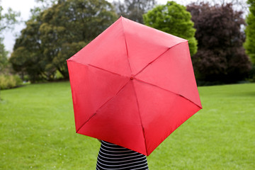 A woman standing in a park, holding a red umbrella, rear view