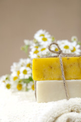 homemade soap bars with camomile flowers and towel,