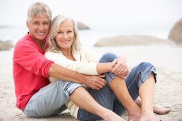 Senior Couple On Holiday Sitting On Winter Beach