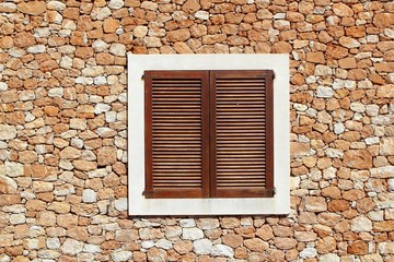 brown wooden window in masonry wall
