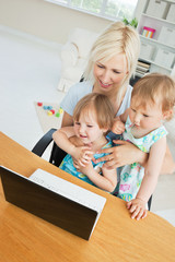 Radiant woman working with her children at laptop