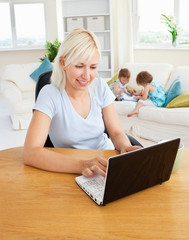 Busy woman working with her children at laptop