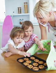 Small girls baking cookies with her mother