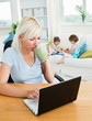 Relaxed working with her children at laptop