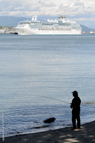 Man fishing while a ship cruises by