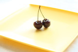 Black cherry in a small bowel on yellow plate poster