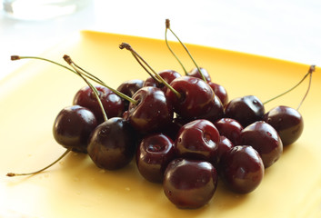 Black cherry in a small bowel on yellow plate
