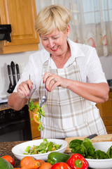 happy woman tossing salad in kitchen