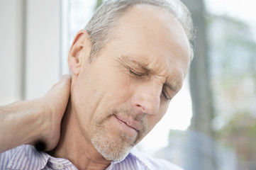 close-up of a man rubbing his neck