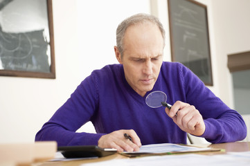 man looking through a magnifying glass while filling his tax form