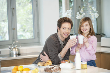 man drinking coffee with his daughter