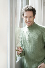 portrait of a man holding the handle of a door