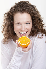 portrait of a woman holding a half of an orange and laughing