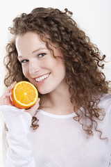 portrait of a woman holding a half of an orange