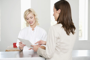 woman with a female nurse examining a medical report