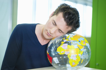 businessman napping on a globe in an office