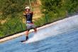 Junger Mann Wakeboarder rast über das Wasser