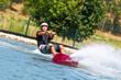 Mann auf Wakeboard strengt sich an