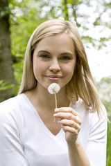 A young woman holding a dandelion clock