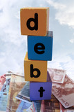 money debt in toy play block letters against clouds