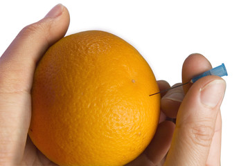 Hand puncturing an orange with a needle