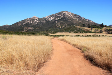 pathway leading to rocky hills,dry grass fields